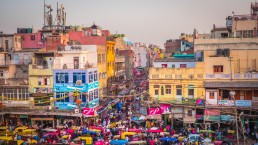 Busy market streets with colorful houses, buildings and crowds of people, rickshaws near Jama Masjid in Old part of New Delhi, India