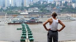 Elderly man overlooks port, Yangtze river. Chongqing, China