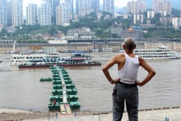 Elderly man overlooks port, Yangtze river. Chongqing, China