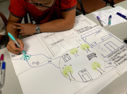 Charlie, a CeNS Board Member, draws his team's idea of a utopian neighbourhood. Credit: CeNS