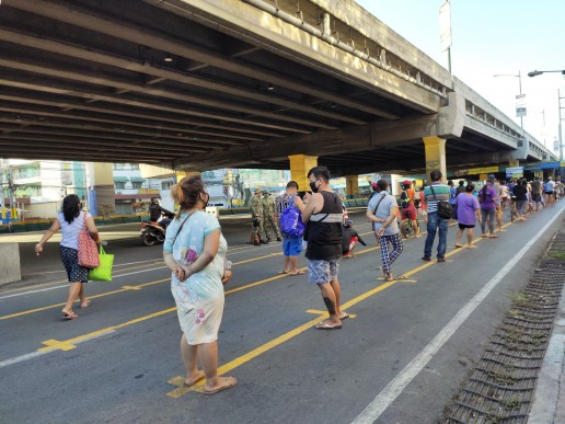 Keeping distance before entering the public market, Philippines. Credit - ILO Asia-Pacific.